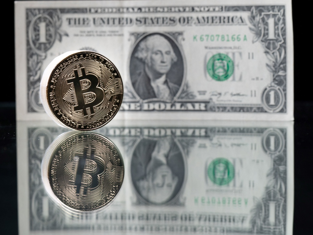 A physical imitation of the Bitcoin cryptocurrency is pictured with a $1 bank note. Cryptocurrencies such as Bitcoin are plunging over a range of factors, including the spillover impact from falling stock markets and fears about increased regulations.