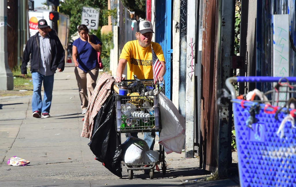 A man pushes a shopping cart full of his belongings in Los Angeles on December 2, 2015.