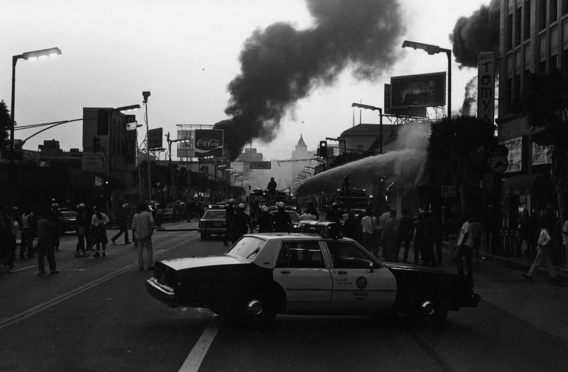 Fire fighters pour water on burning stores during the riots on April 30, 1992. A police car is in the foreground.