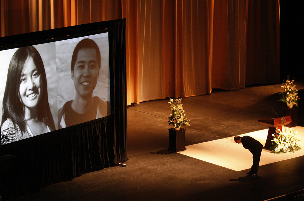 USC Prseident C. L. Max Nikias bows before images of victims Ying Wu and Ming Qu before eulogizing the slain engineering students during a memorial service in the Shrine Auditorium on Wednesday, April 18, 2012 in Los Angeles. The Chinese students were shot to death while sitting in their parked car near the campus last week. (AP Photo/Los Angeles Times, Luis Sinco, Pool)