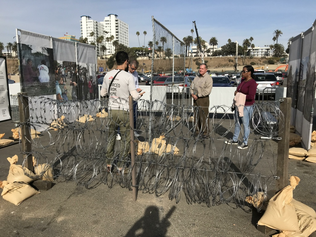 The barbed wire barricades are meant to represent what refugees have to deal with as they flee their home countries.