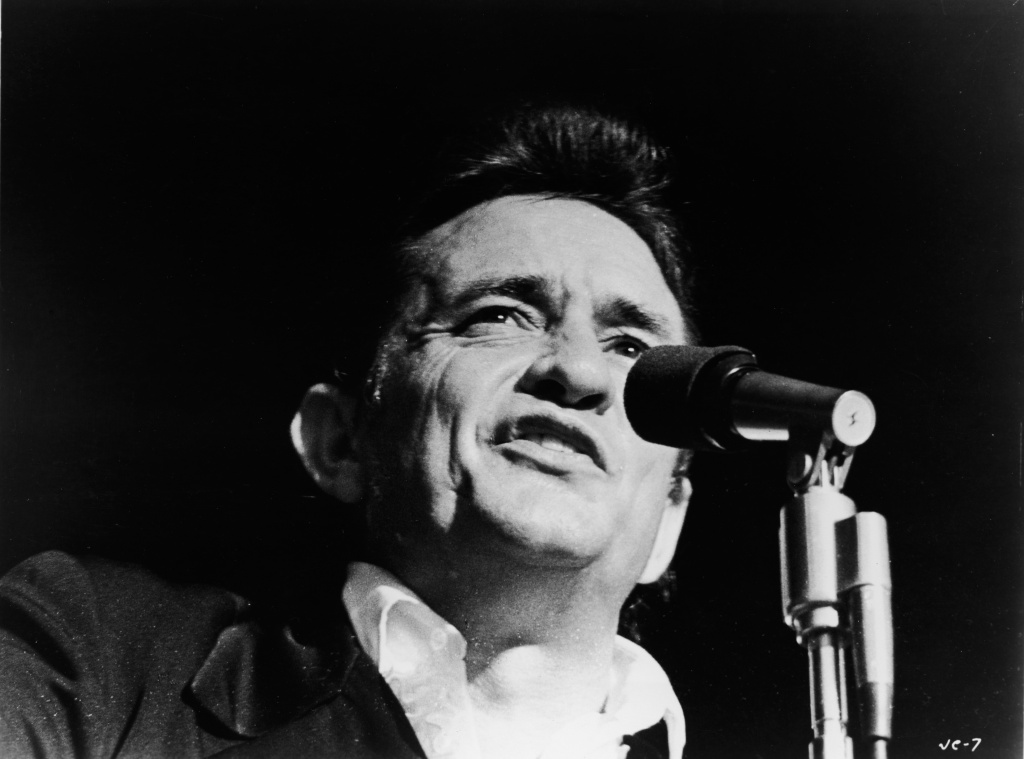 Headshot of American country singer Johnny Cash singing on stage in a still from the film,