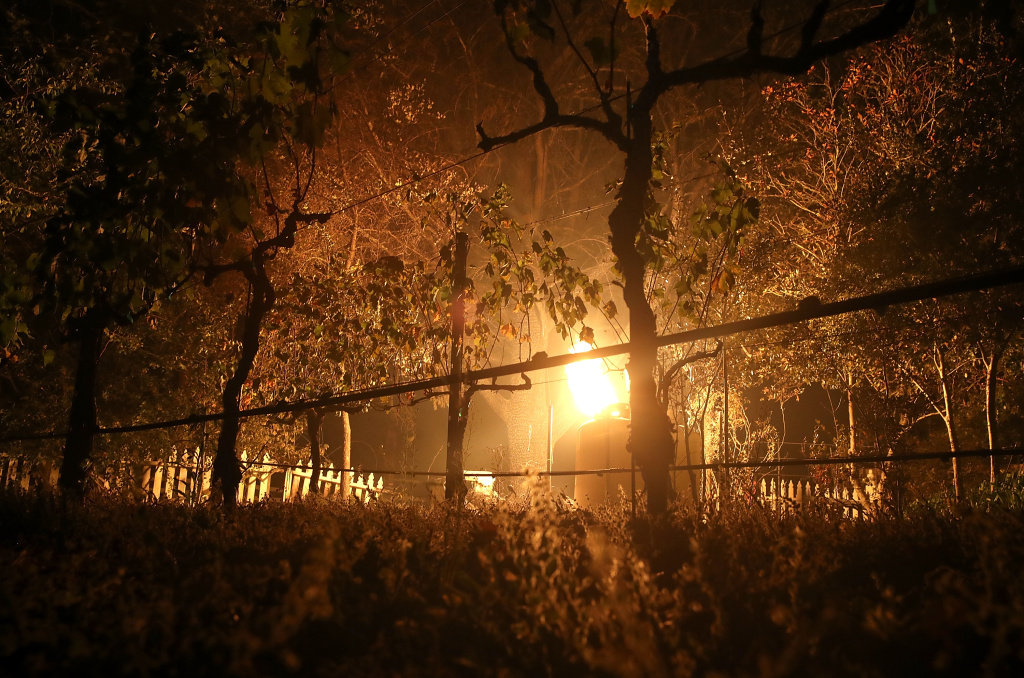 A flame from an open gas line illuminates grape vines in a vineyard during the Nuns Fire on October 9, 2017 in Glen Ellen, California.