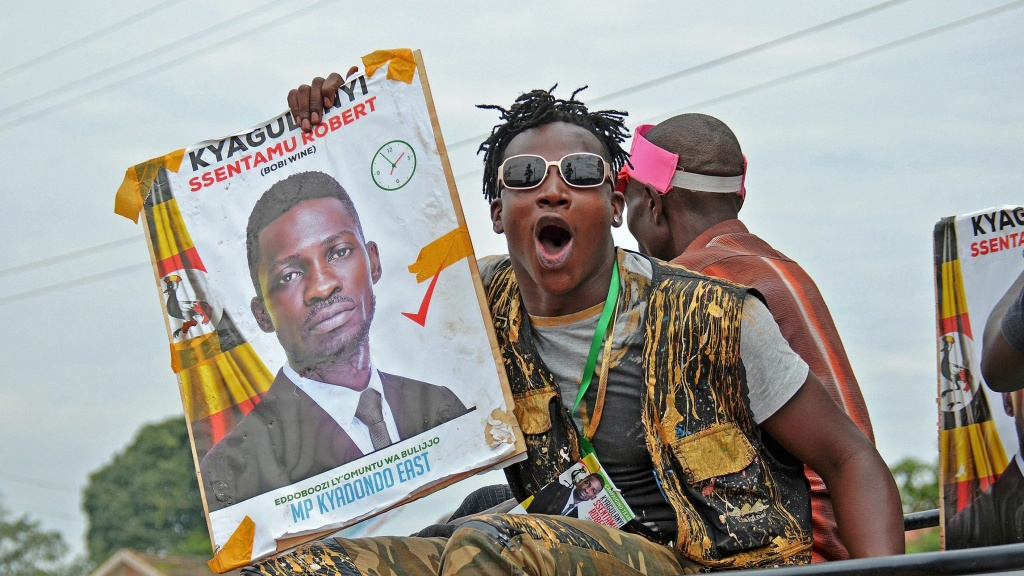 A supporter holds a poster of musician-turned-politician Robert Kyagulanyi, better known as Bobi Wine, in a suburb of Kampala on June 29, 2017. Wine was imprisoned and allegedly tortured following a demonstration against Ugandan President Yoweri Museveni, prompting prominent artists to issue an open letter calling for his release.