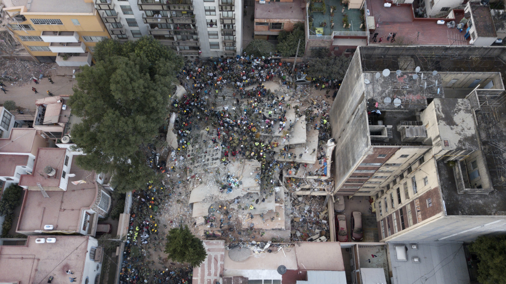 Rescue workers and volunteers search for survivors on a collapsed building the Del Valle neighborhood in Mexico City, Tuesday Sept. 19, 2017. A magnitude 7.1 earthquake has stunned central Mexico, killing more than 100 people as buildings collapsed in plumes of dust. (AP Photo/Miguel Tovar)
