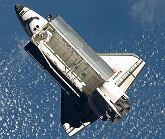 Space shuttle Atlantis flies around the International Space Station after undocking.