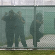Female detainees stand at the fence in the exercise yard inside Homeland Security's Willacy Detention Center in Raymondville, Texas, May 10, 2007. Federal officials are proposing a new immigrant detention center in South Texas, one that would house families, in response to the recent Central American migrant crisis at the border. The government was sued over inhumane conditions at a different family detention center in Texas in 2007.
