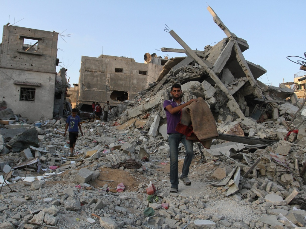 Palestinians carry belongings from their homes, destroyed by Israeli airstrikes, in Beit Hanoun in the northern Gaza Strip on Sunday. The devastation could resume if a cease-fire is allowed to expire at midnight on Monday.
