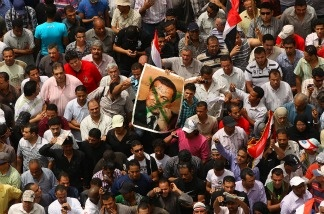 Demonstrators hold a placard with a crossed out photograph of former President Hosni Mubarak in Tahrir Square on May 27, 2011 in Cairo, Egypt.