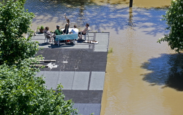 Residents sit on the roof of a garage flooded by the river Elbe in Dresden, eastern Germany, on June 5, 2013. Flooding has forced tens of thousands of evacuations across central Europe. (Photo by Robert Michael/AFP/Getty Images)