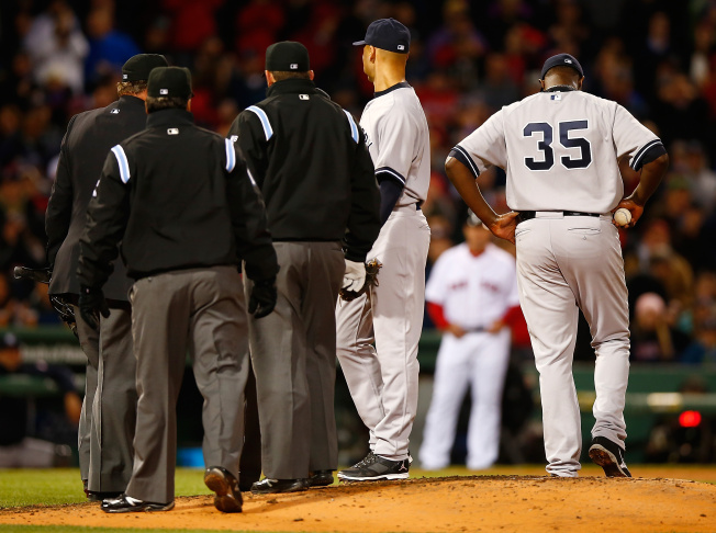 Home plate umpire Gerry Davis throws out Michael Pineda #35 of the New York Yankees after finding a substance on him in the second inning against the Boston Red Sox during the game at Fenway Park on April 23, 2014 in Boston, Massachusetts.