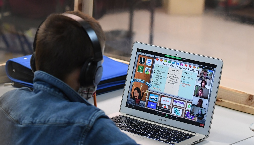 Students follow along remotely with their regular school teacher's online live lesson from a desk wrapped in protective plastic at STAR Eco Station Tutoring & Enrichment Center on September 10, 2020 in Culver City, California.