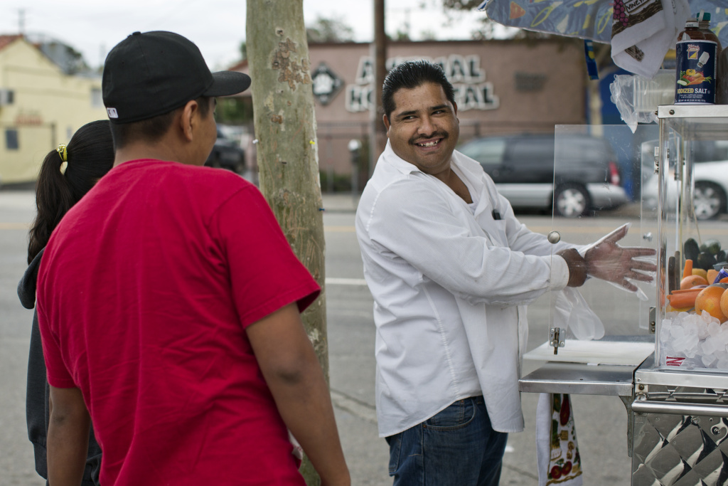 Delfino Flores prepares fresh fruit for customers Ana Ruiz and Armando Arizpe on Figueroa Street in Highland Park on Tuesday, Nov. 11, 2014.