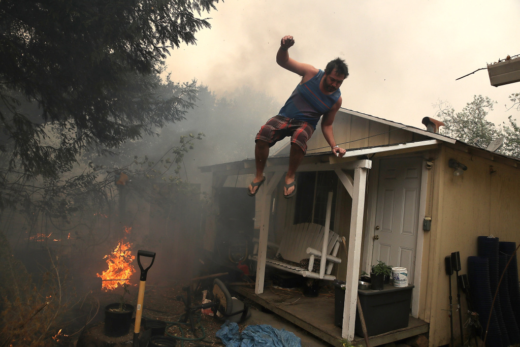 A resident rushes to save his home as an out of control wildfire moves through the area on Oct. 9, 2017 in Glen Ellen, California. Tens of thousands of acres and dozens of homes and businesses have burned in widespread wildfires that are burning in Napa and Sonoma counties.