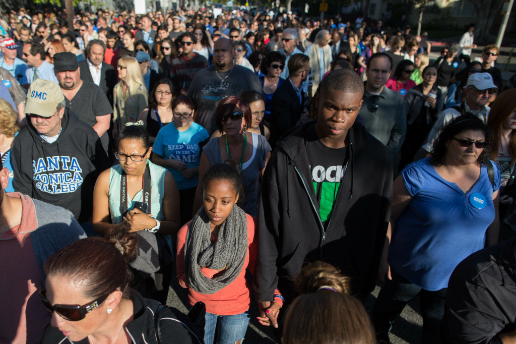 Hundreds participate in a silent march to Corsair Field for a vigil in honor of five people killed by a gunman at Santa Monica College.