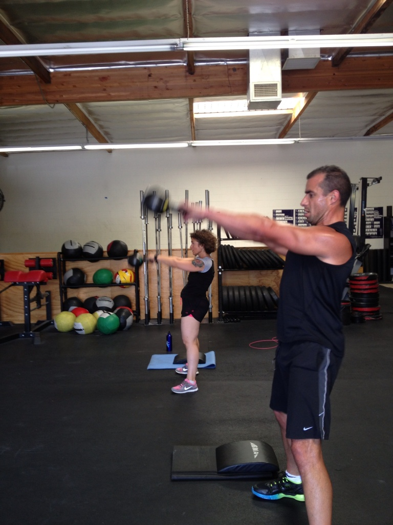 KPCC's Alex Cohen and A Martinez do a CrossFit workout. CrossFit is one of a wide range of options for those resolving to exercise in the new year.