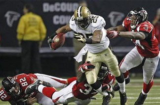 The Atlanta Falcons defense tries to take down New Orleans Saints running back Reggie Bush (25) in the first half of an NFL football game at the Georgia Dome in Atlanta on Monday, Dec. 27, 2010. Defending for Atlanta are Joe Zelenka (82), Ovie Mughelli (34) and Jason Snelling (44).
