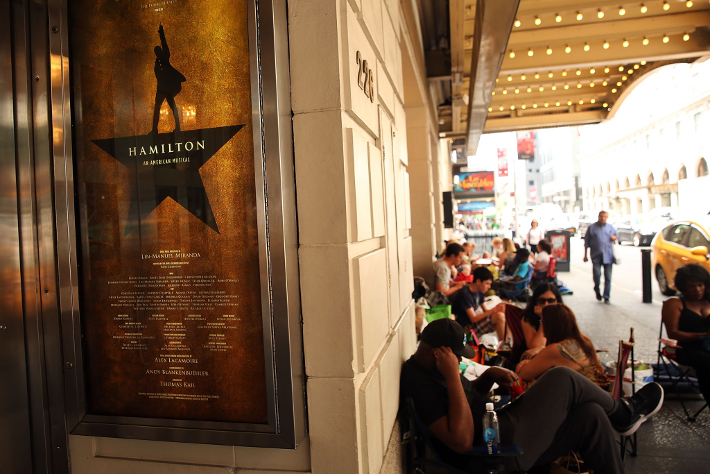 NEW YORK, NY - JUNE 21:  People, many who have been there for days, wait in line with dozens of others for tickets for the popular Broadway show Hamilton on June 21, 2016 in New York City. The Tony Award-winning Broadway hit has drawn huge crowds to the Richard Rogers theater in the hopes of getting increasingly scarce and expensive tickets. Carrying bed rolls, pillows and take-out food containers, many fans of the musical wait days in the heat and rain for a chance to get a cancellation ticket which are offered to the public once they're declined by members of the cast and crew.  (Photo by Spencer Platt/Getty Images)