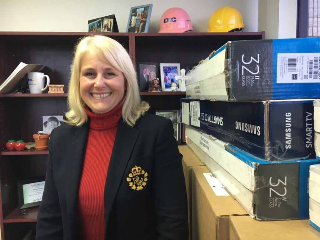 Donna Gallup, president and CEO of American Family Housing, in her office next to boxes of donated televisions that will go into the apartments at Potter's Lane. The non-profit is overseeing the housing project in Midway City located next to its offices, where counselors will maintain regular contact with the veterans who move in next door.