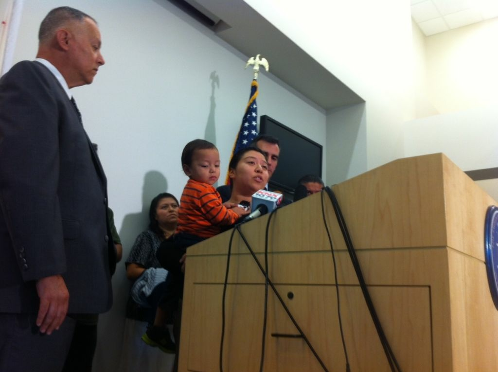 Ana Mendez, holding her son, asks for witnesses to come forward in the murder of her husband, Andres Ordonez.