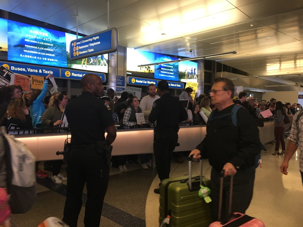 Police arrive to calm protesters at the LAX international terminal Saturday night, Jan. 28, 2017. Chanting