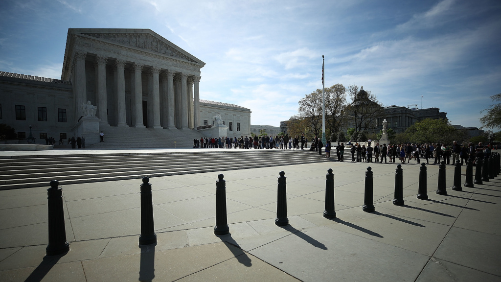 People wait in line to enter the U.S. Supreme Court last month. The court sided with businesses on not allowing class-action lawsuits for federal labor violations.