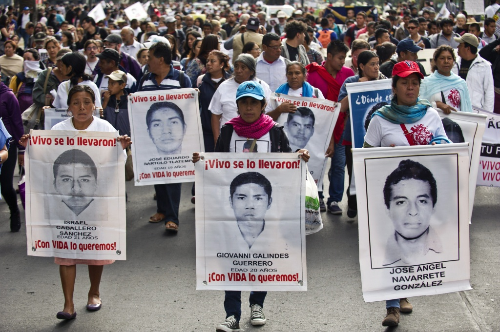 Relatives and friends of the 43 missing students from Ayotzinapa hold their portraits in Mexico City on March 26, 2015. Federal police said they'd captured an associate of the of the leader of the drug gang that prosecutors allege kidnapped and killed the students and incinerated their remains.