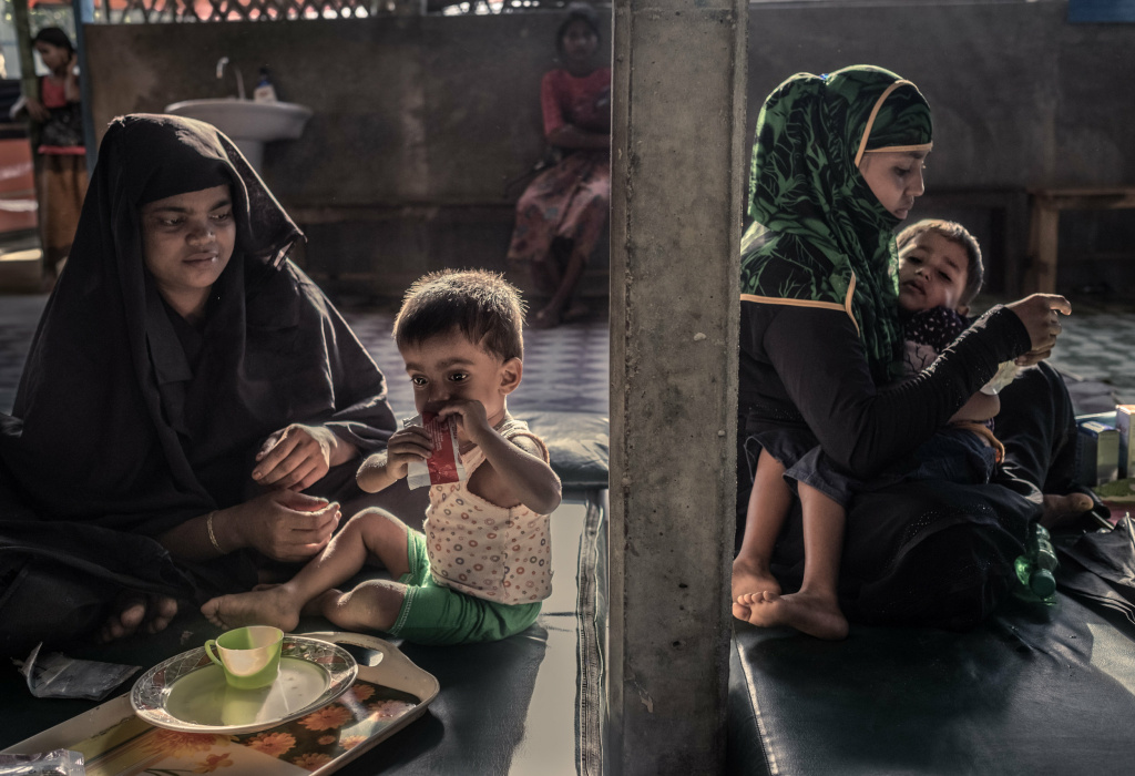 Rohingya refugees feed their malnourished children at a feeding center in Kutupalong camp.