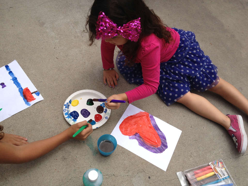 5-year old Ariana Gonzalez paints a heart as she and her sister hang out at home during the summer.
