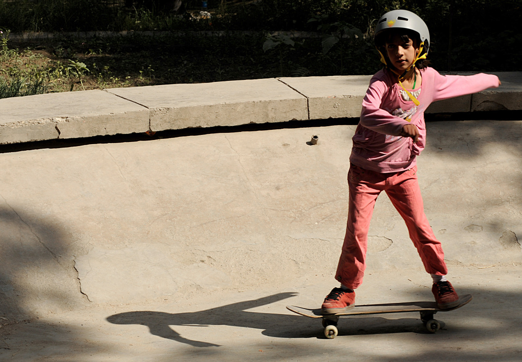 An Afghan girl rides a skateboard inside the bowl of an old concrete fountain during the celebration of International Go Skateboarding Day in Kabul on June 21, 2009.