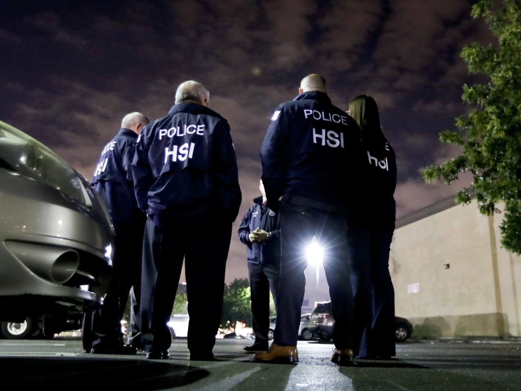 U.S. Immigration and Customs Enforcement agents gather before serving a employment audit notice at a 7-Eleven convenience store in Los Angeles in January.