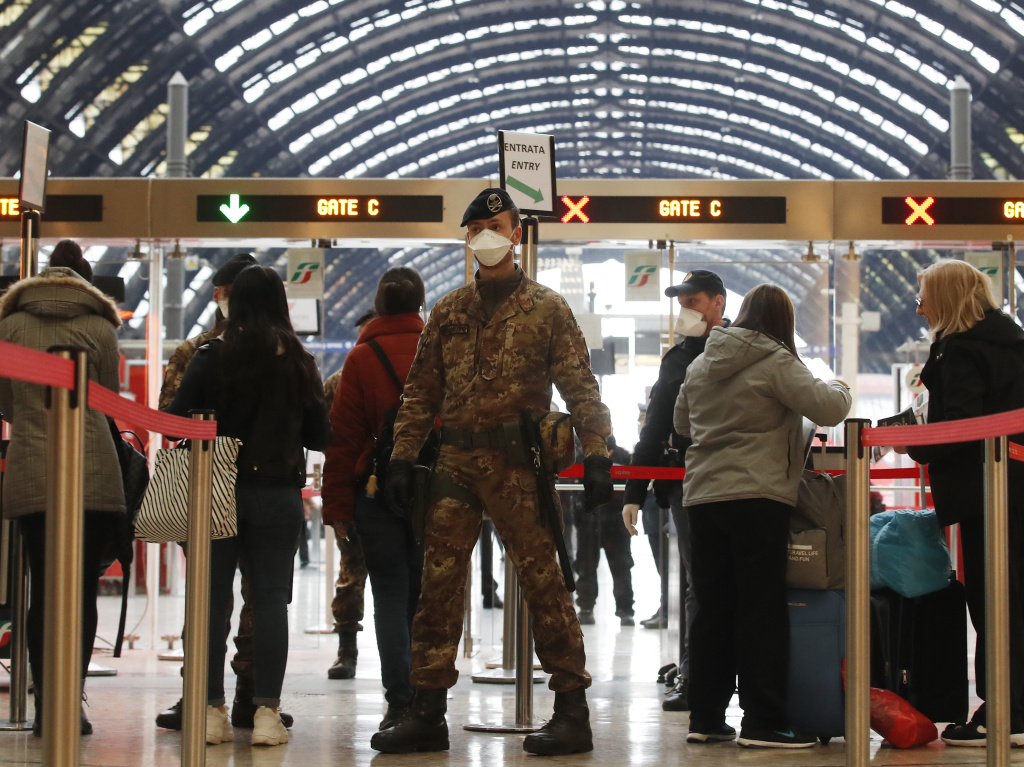 In Italy, police officers and soldiers check passengers leaving from Milan's main train station on Monday.