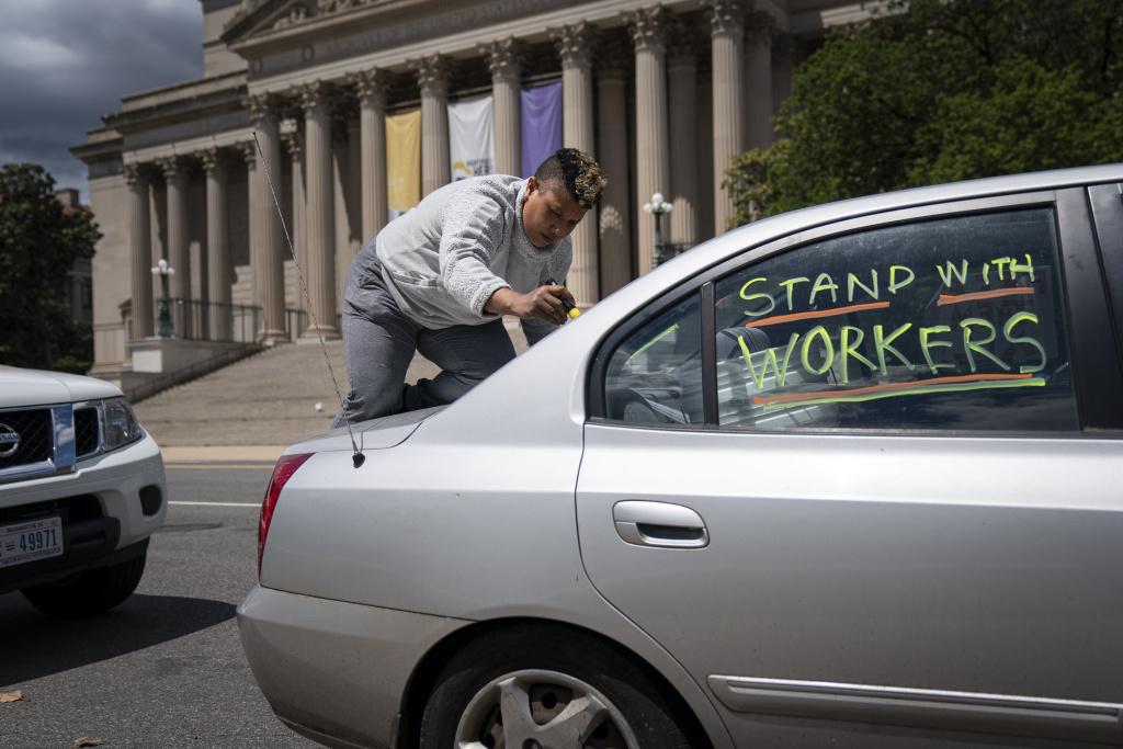 An activist writes messages on her vehicle as she participates in a May Day protest during the coronavirus pandemic, May 1, 2020 Washington, DC.