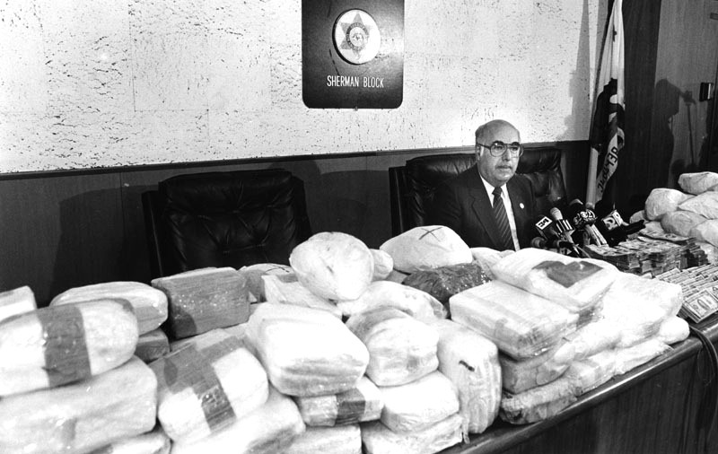 File: LA County Sheriff Sherman Block, who served from 1982-1998, dying in office, displays 411 pounds of cocaine seized in one of Los Angeles County's largest drug busts.