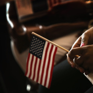 "Vishaun Lawrence of Jamaica, a new U.S. citizen, holds an American flag along with her citizenship papers as she participates in a naturalization ceremony at the Chicago Cultural Center on July 3, 2013 in Chicago, Illinois. Los Angeles has joined Chicago and New York in a new ""Cities for Citizenship"" project, funded by $1.1 billion from corporate partner Citigroup. Funds will go toward support services for legal residents who hope to become naturalized citizens."