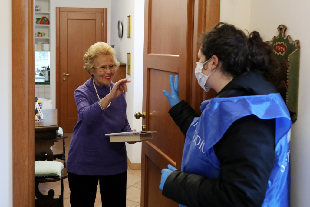 A volunteer from the Community of Sant'Egidio, speaks to an elderly woman during a home-care service on March 16, 2020 in Rome, Italy.