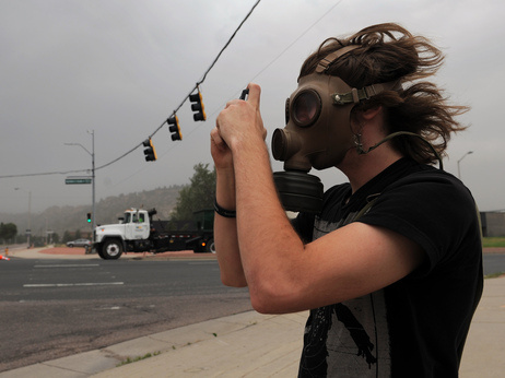 Mikke Carlson took photos of the smoke from the Waldo Canyon fire while wearing a gas mask on Wednesday, June 27, 2012, in Colorado Springs, Colo.