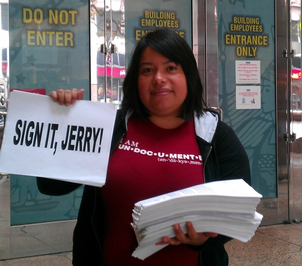 UCLA graduate and California Dream Act supporter Nancy Meza holds petitions in downtown Los Angeles, Wednesday, October 5, 2011