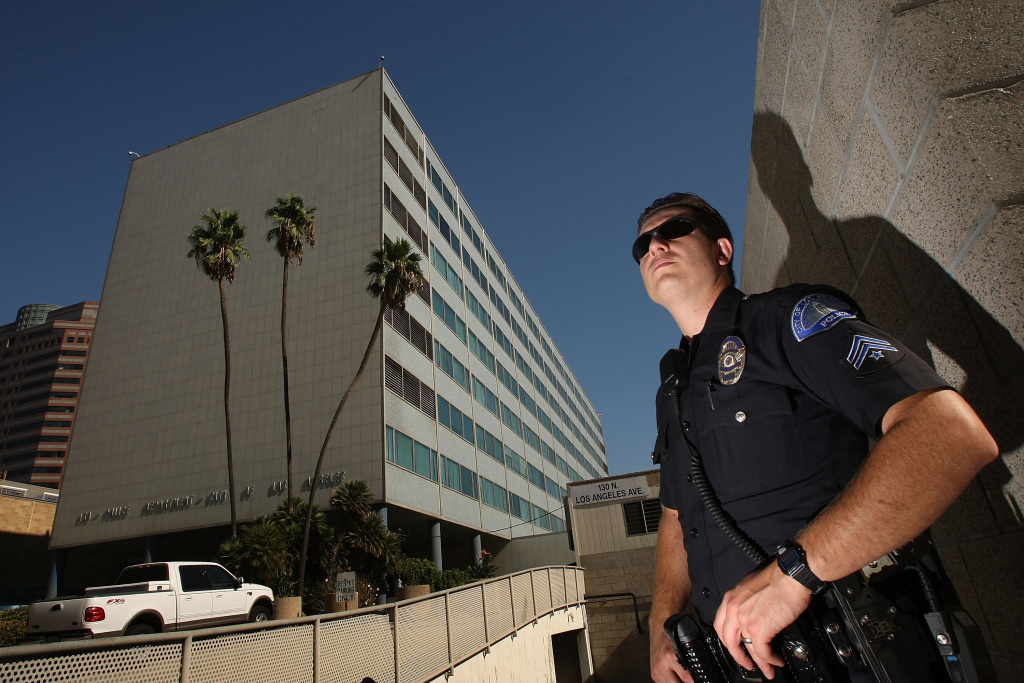 A Los Angeles police officer stands guard outside Parker Center (L), headquarters for the Los Angeles Police Department (LAPD) on October 8, 2008 in Los Angeles, California.