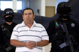 Alleged drug trafficker Jose Antonio Medina, aka 'Don Pepe', is escorted by police officers during a press conference in Mexico City on March 25, 2010. Medina was arrested recently in Michoacan State.
