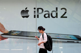 File photo: A woman checks her cell phone while walking past advertising for the ipad 2 in Beijing on June 3, 2011.