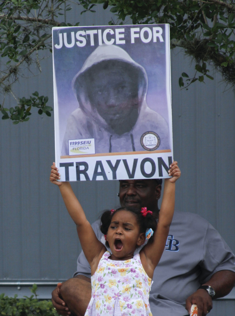 Hanna Brianna, 5, holds a sign in front of her home in the Goldsboro Historical neighborhood, Saturday, July 13, 2013, in Sanford, Fla. while residents wait for word on the verdict in the George Zimmerman trial. Zimmerman is charged with the 2012 shooting death of Trayvon Martin. (AP Photo/Mike Brown)