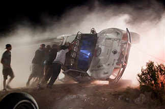 Workers push an overturned off-road race truck upright Sunday after it went out of control and plowed into a crowd of spectators during a race earlier in Lucerne Valley, Calif., Saturday, Aug. 14, 2010. At least eight people were killed during the incident about 100 miles east of Los Angeles.