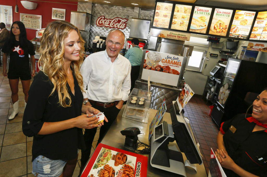 File: Sports Illustrated swimsuit model Hannah Ferguson, left, orders lunch alongside CKE Restaurants CEO Andy Puzder after a news conference on Wednesday, Aug. 6, 2014 in Austin, Texas declaring Carl's Jr.'s commitment to the state of Texas.