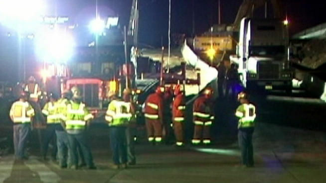 Workers and rescuers at the site of a fatal construction accident on the 405 Freeway.