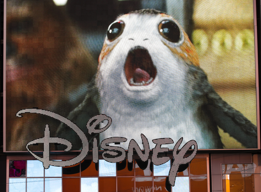 An advertisement of the new Star Wars film plays on a screen as the Disney logo is displayed outside the Disney Store in Times Square, December 14, 2017 in New York City.