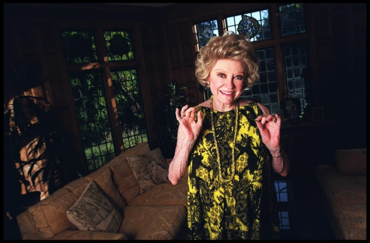 Phyllis Diller poses with her photos at her home in the Brentwood section of Los Angeles, Friday, March 11, 2005. Female standup comics had never made the big-time, but Diller beat the odds, paving the way for Lily Tomlin, Rosanne, Ellen DeGeneres and others to follow.