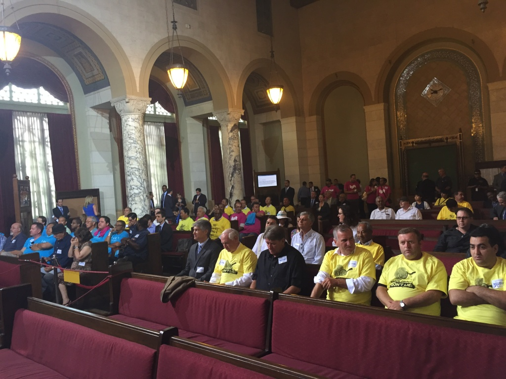 Taxi supporters in yellow and Uber and Lyft supporters in blue and pink pack the chambers of City Council for Tuesday's vote on whether to allow rideshare at LAX.