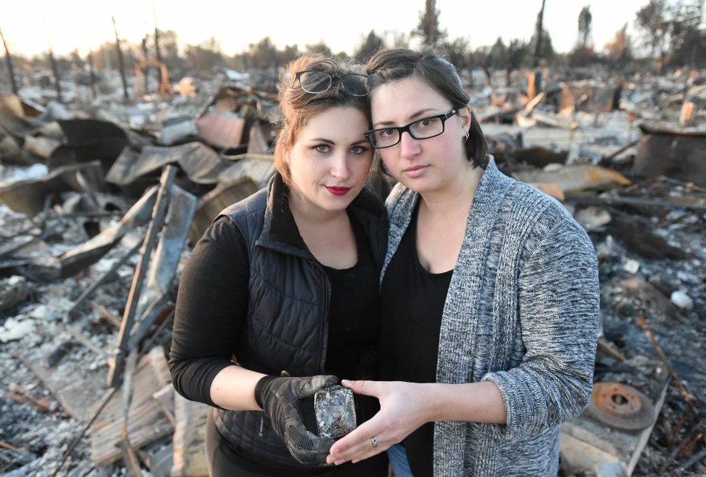 Michelle Ross (L) and Stephanie Staykow (R) pose for a photo while holding their baptism crosses they found in the remains of their burned home in Santa Rosa, California on October 20, 2017.  Residents are being allowed to return to their burned homes on October 20 to grieve and search through remains. Around 5,700 homes and businesses have been destroyed by the fires, the deadliest in California's history. / AFP PHOTO / JOSH EDELSON        (Photo credit should read JOSH EDELSON/AFP/Getty Images)