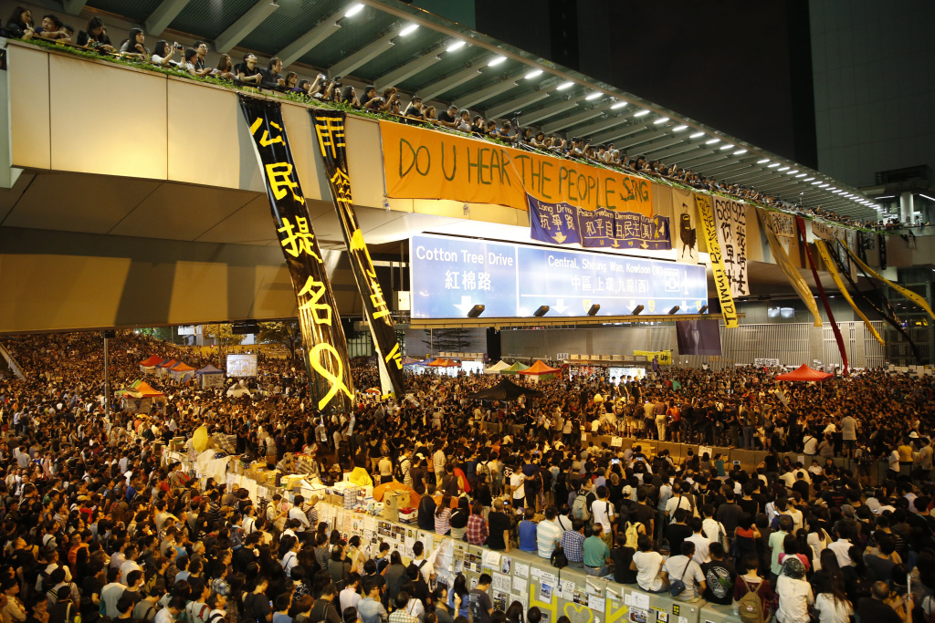 Pro-democracy protesters attend a rally in the occupied areas outside government headquarters in Hong Kong's Admiralty, Friday, Oct. 10, 2014. Thousands of people are pouring into a main road in Hong Kong to show support for a pro-democracy protest after the government called off talks with student leaders. (AP Photo/Kin Cheung)